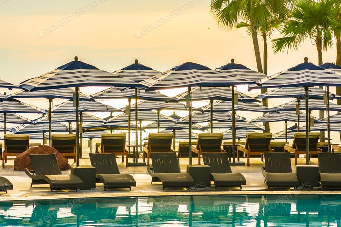Umbrella and chair sofa around outdoor swimming pool in hotel re