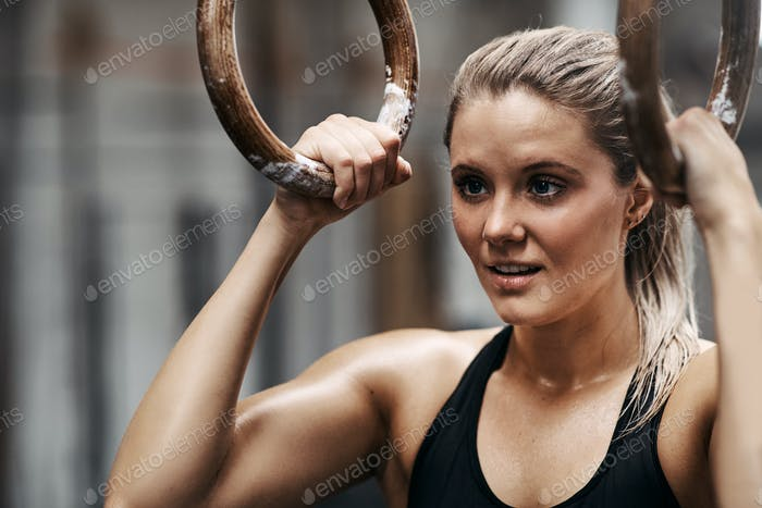 Smiling young woman exercising with rings at the gym