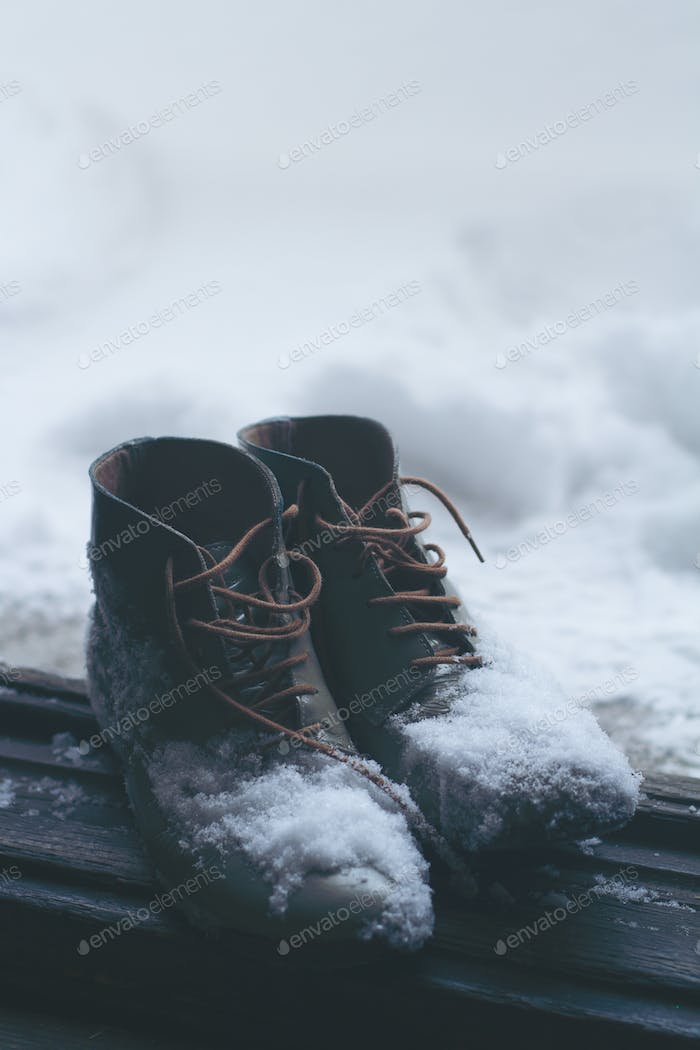 vintage leather shoes covered in snow by the door