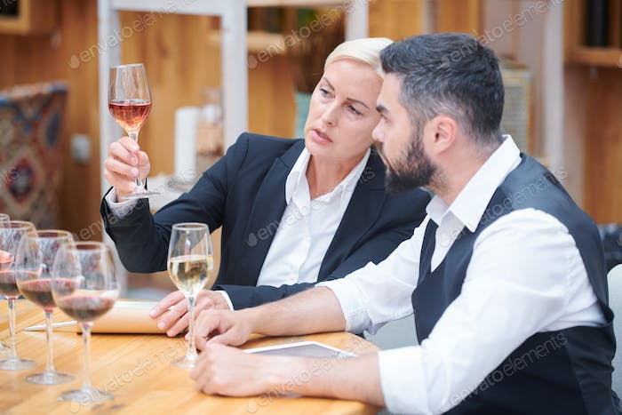 Pretty sommelier with glass of white wine giving its chracteristics