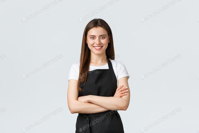Fröhlich lächelnd weibliche Barista in schwarzer Schürze Kreuz Arme Brust, suchen bereit und zuversichtlich. Jung