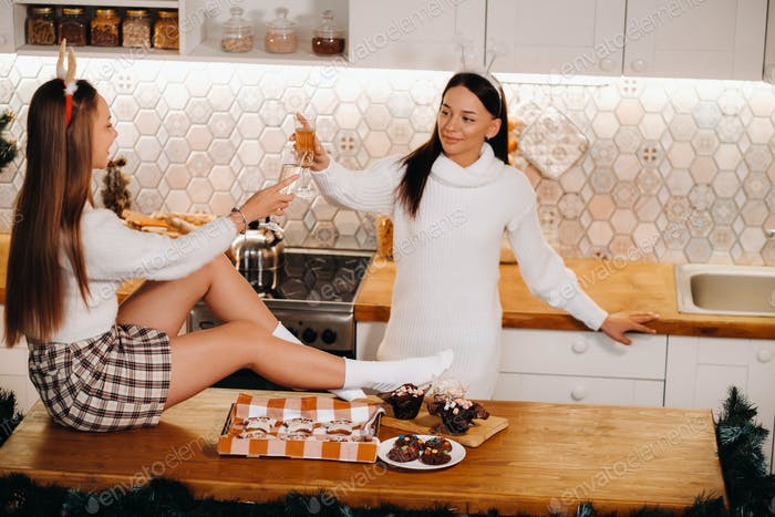 zwei Mädchen in einer gemütlichen Wohnumgebung in der Küche mit Champagner in den Händen zu Weihnachten