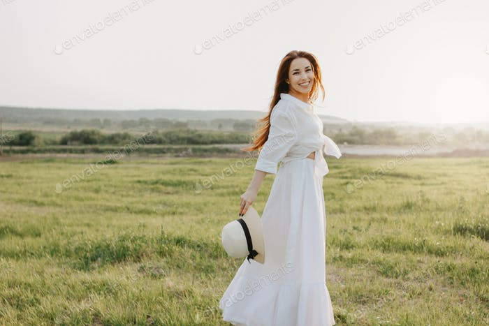 Beautiful carefree long hair asian girl in white clothes and straw hat enjoys life at field