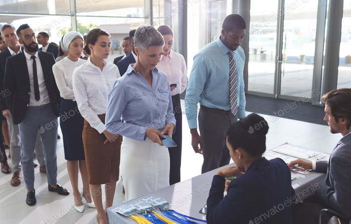 Side view of business people checking in at conference registration table in office
