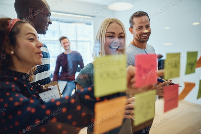 Smiling designers brainstorming together on an office wall