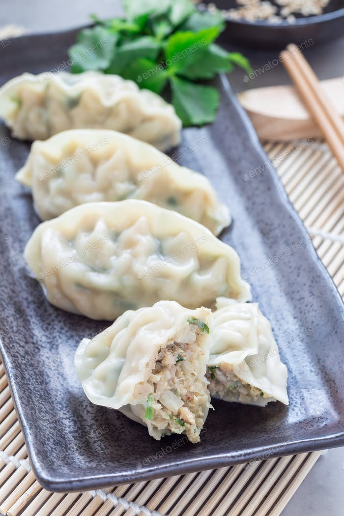 Steamed Korean dumplings Mandu with chicken meat and vegetables on black plate, vertical