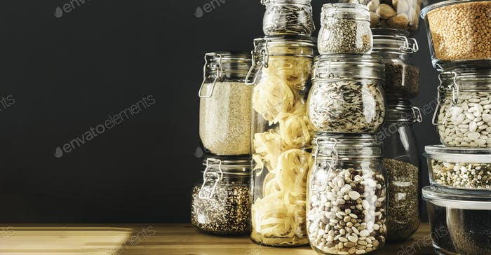 Banner with assortment of uncooked grains, cereals and pasta in glass jars on wooden table. Healthy