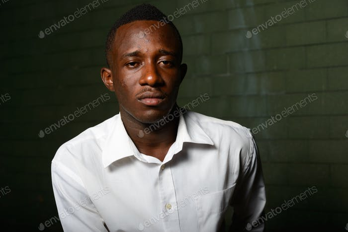 Young African businessman against brick wall in the dark