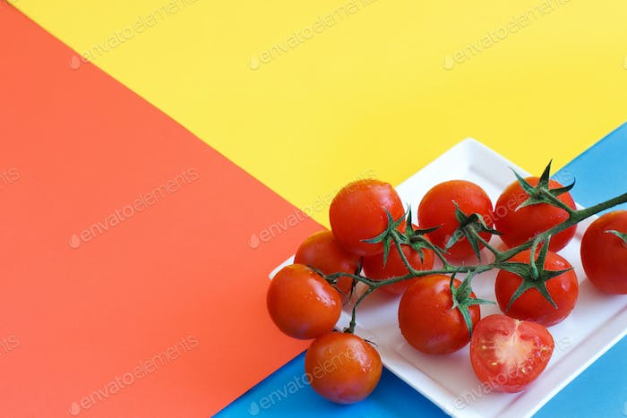 Cherry tomatoes on a blue, yellow and coral red background