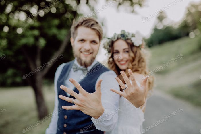 Bride and groom with wedding rings in nature.
