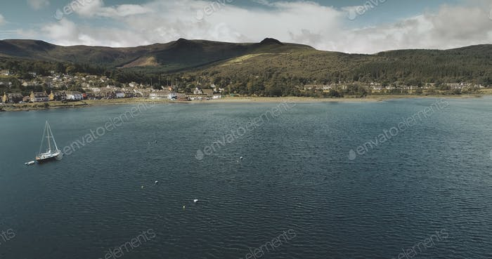 Atlantic ocean gulf, sailboats aerial zooming shot in Brodick Bay. Scottish landscape of port town