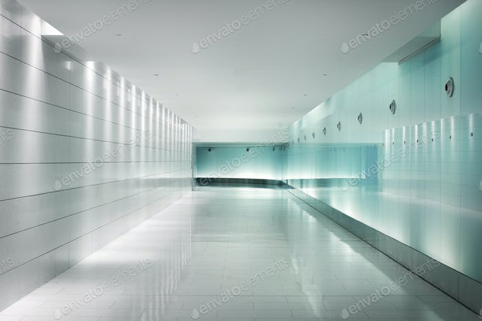 Back-lighted glass walls in an underground futuristic corridor