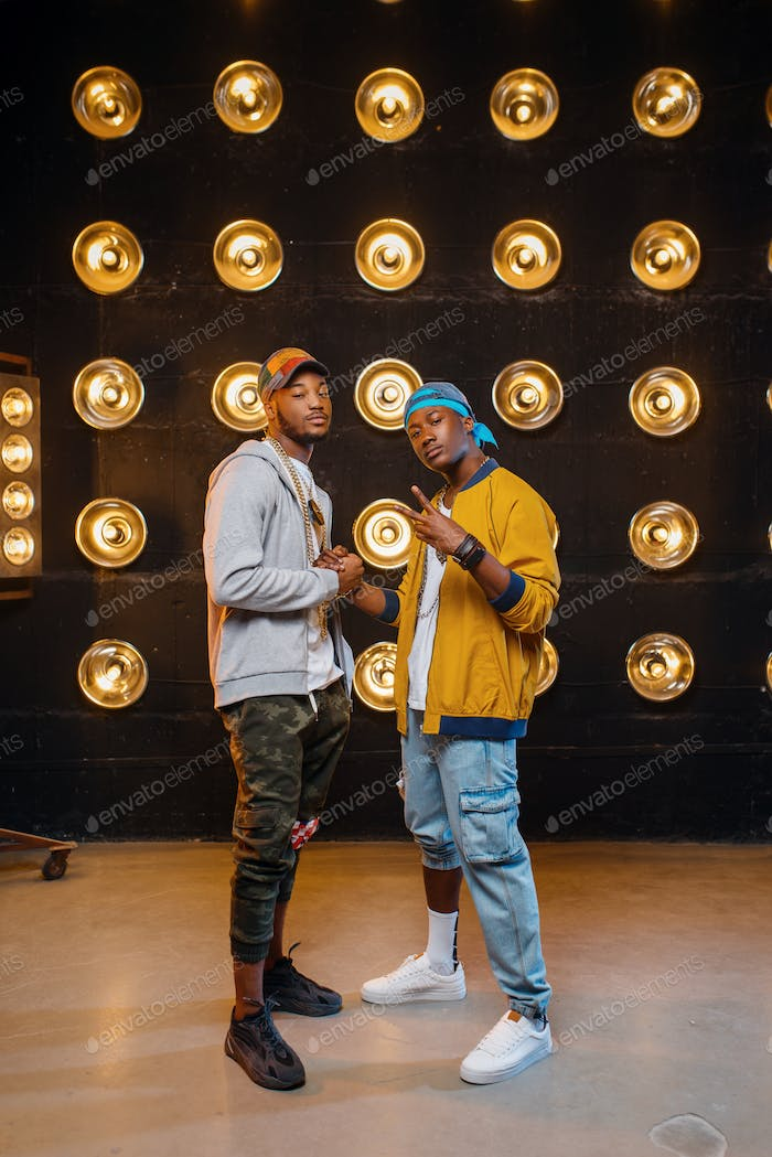 Two black rappers in caps, artists poses on stage