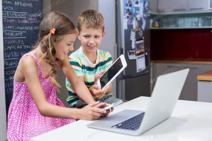 Boy showing digital tablet to girl in kitchen