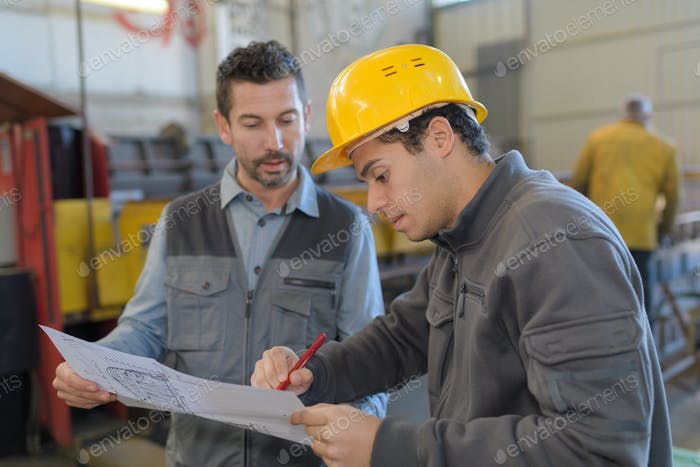 worker in uniform showing his boss the plan of factory