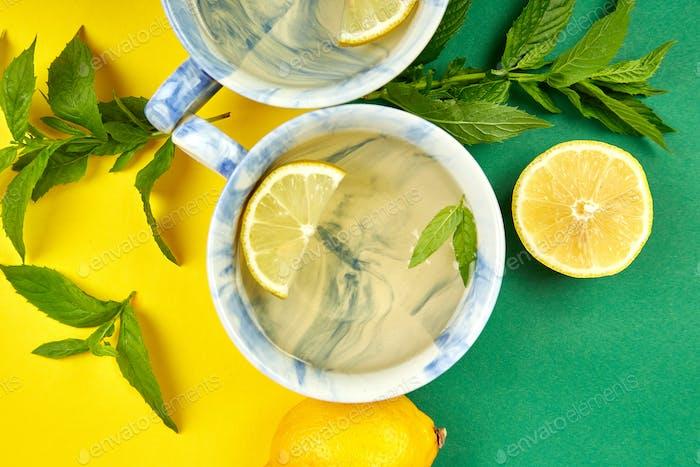 Gesunder Tee zwei Tassen mit Zitrone, Ingwer, Minze