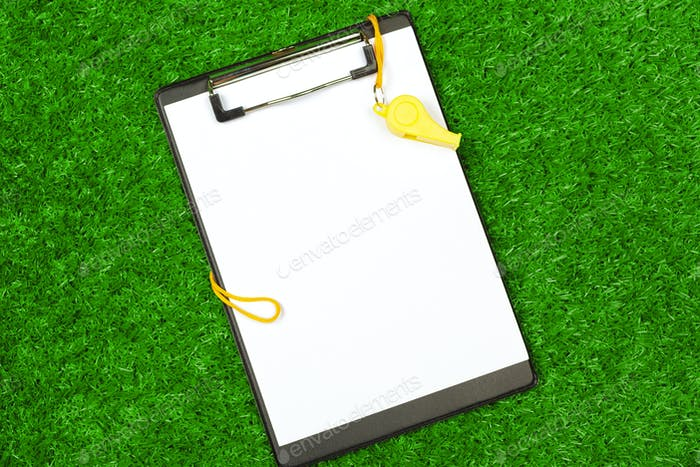 Sheet of paper and sports equipment on grass close-up