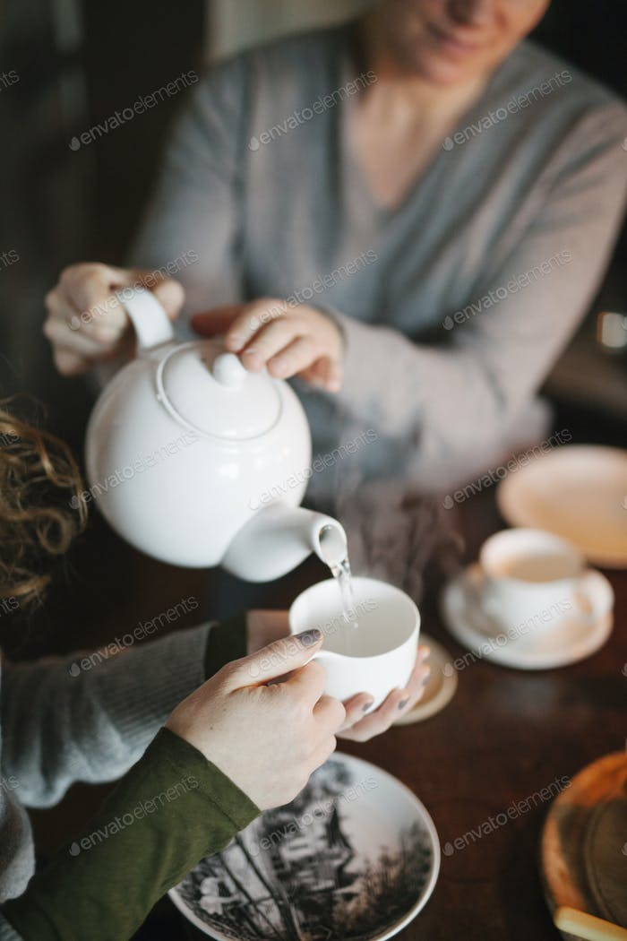 A woman pouring tea from a teapot into a cup for a companion.