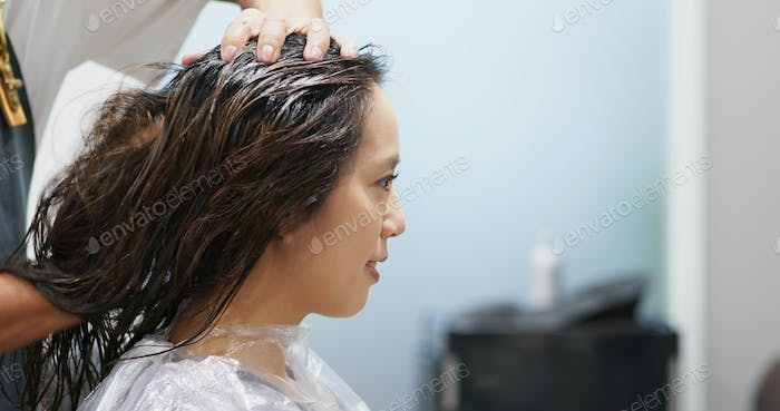 Woman having colour dyeing at hair salon