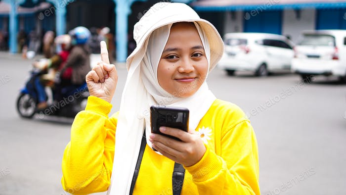 Asian female traveler pointed up with a camera holding a cellphone wearing jilbab and analog camera