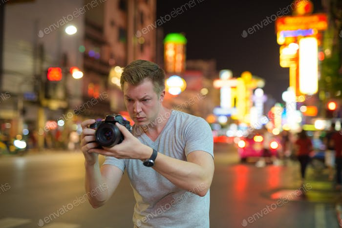 Young tourist man photographing with camera in the streets of Chinatown at night