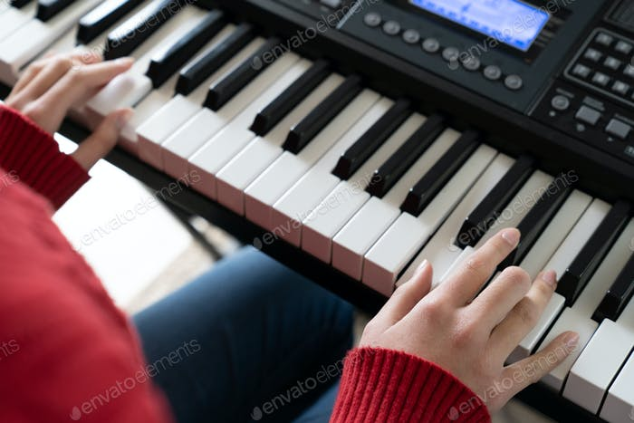 Little girl hand playing piano keyboard
