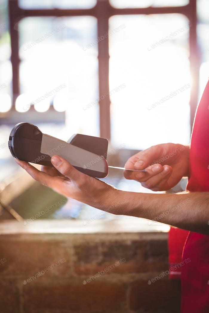 Kellner Einlegen der Kreditkarte des Kunden in die Kreditkartenmaschine