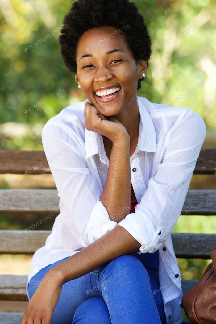 Attractive young african woman sitting on park bench
