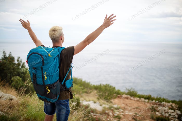 Happy man on mountain enjoying landscape. Travel, vacation, adventure, freedom concept