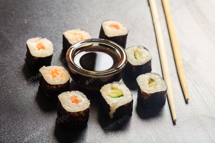 Sushi rolls on a black surface