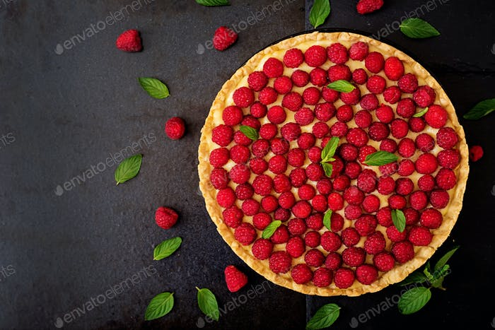 Tart with raspberries and whipped cream decorated with mint leaves on a black background. Top view
