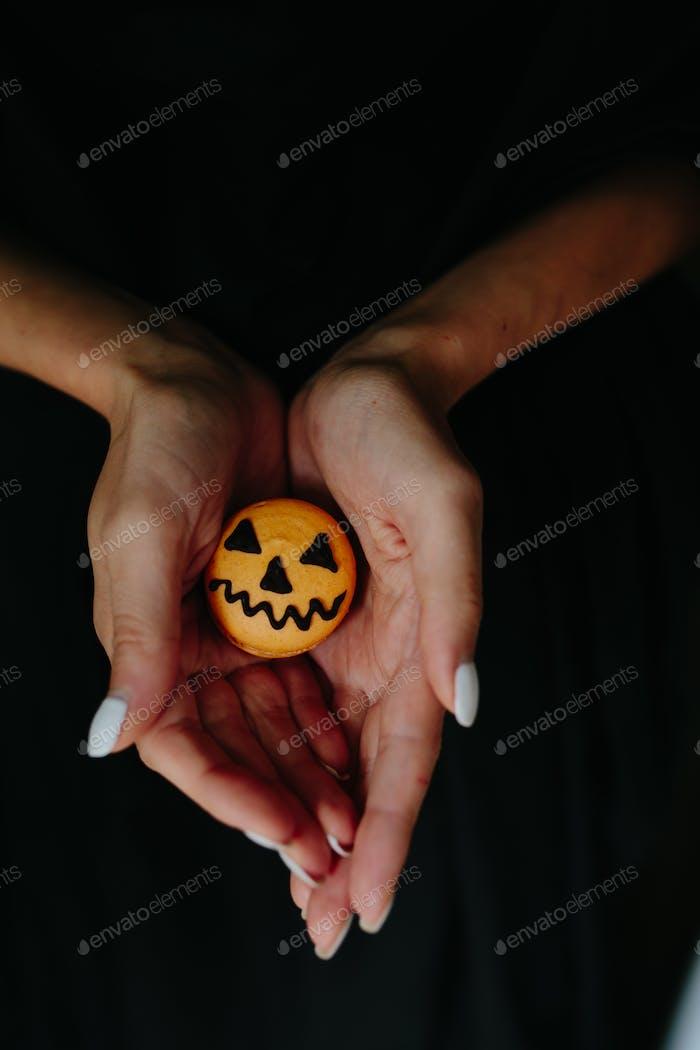 Frau hält einen Keks für Halloween