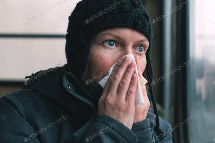 Woman blowing her nose into paper handkerchief