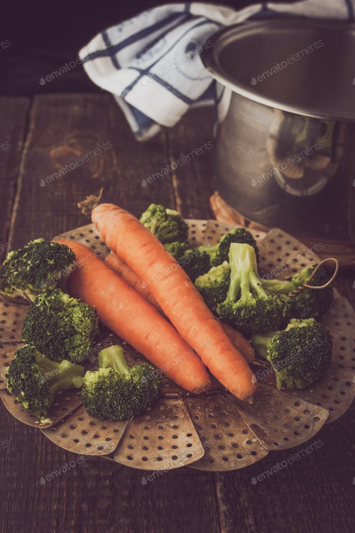 Steamed carrots and broccoli on the wooden table