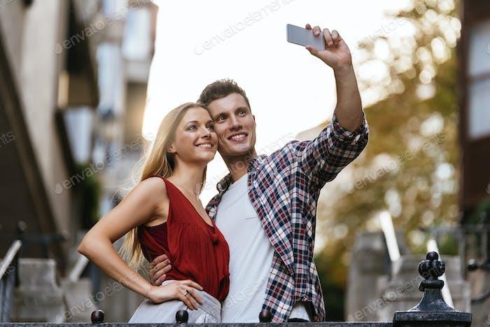 Romantisches junges Paar, das ein Foto mit Handy macht.