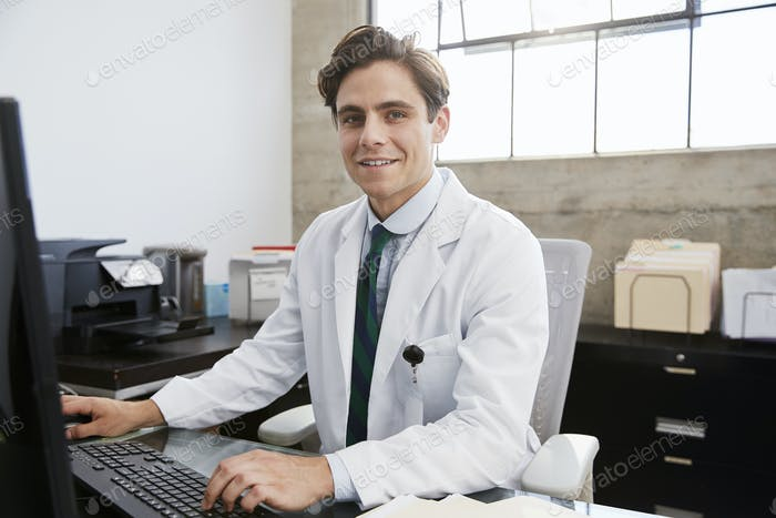 Young white male doctor using computer smiling to camera
