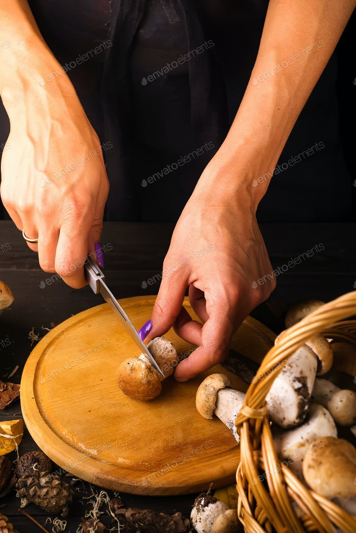 female hands cut fresh forest mushrooms on a wooden board over dark a wooden background