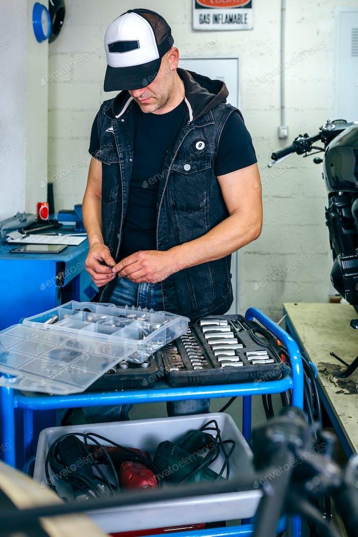 Mechaniker wählt Schrauben aus einem Werkzeugkasten