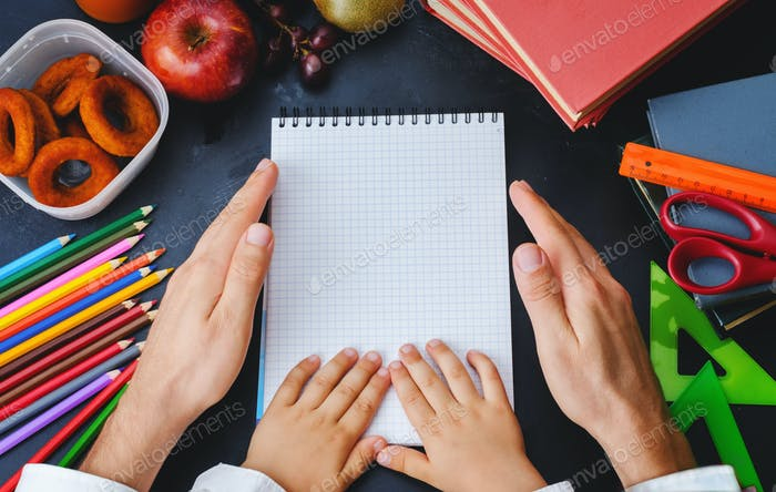 Mens and childrens hands holding a notebook. School concept.