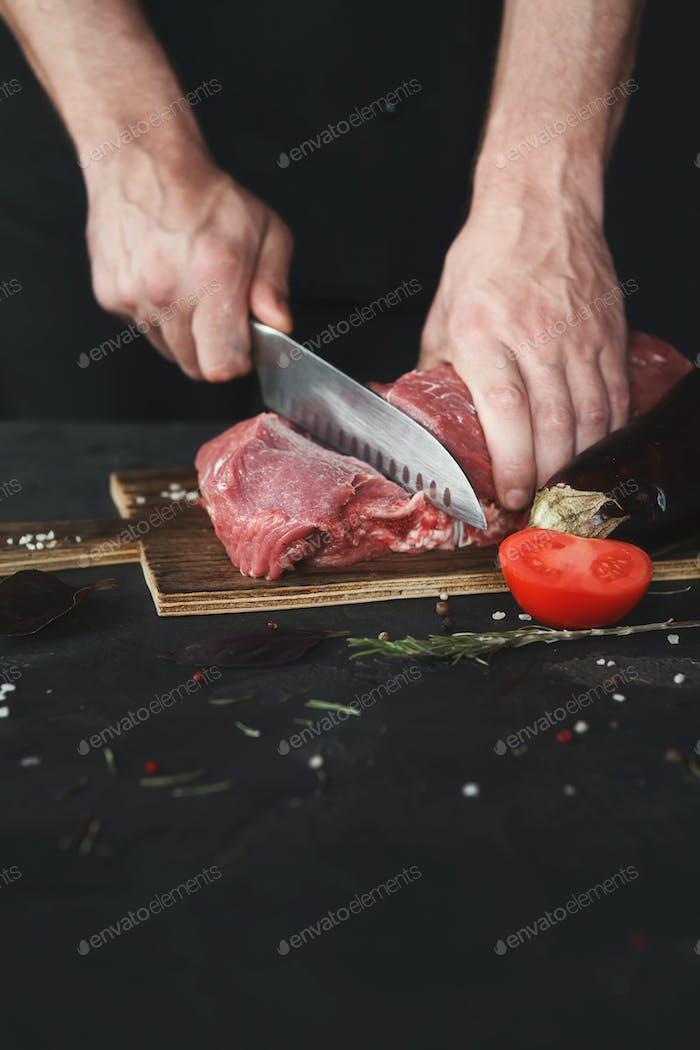 Küchenchef Schneidefilet Mignon auf Holzbrett in der Restaurant-Küche