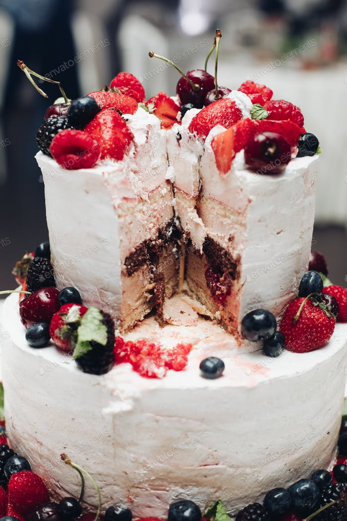 Beautiful wedding cake with berries.Sliced wedding cake in close-up