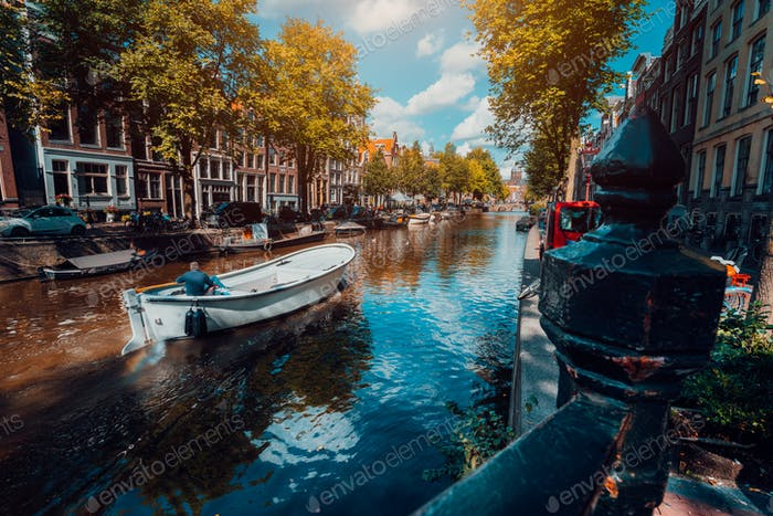 Channel in Amsterdam in autumn sunlight. Boat floating tree-lined canal, vibrant reflections, white