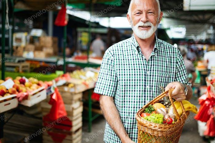 Positive elderly man buying seasonal vegetables in local market