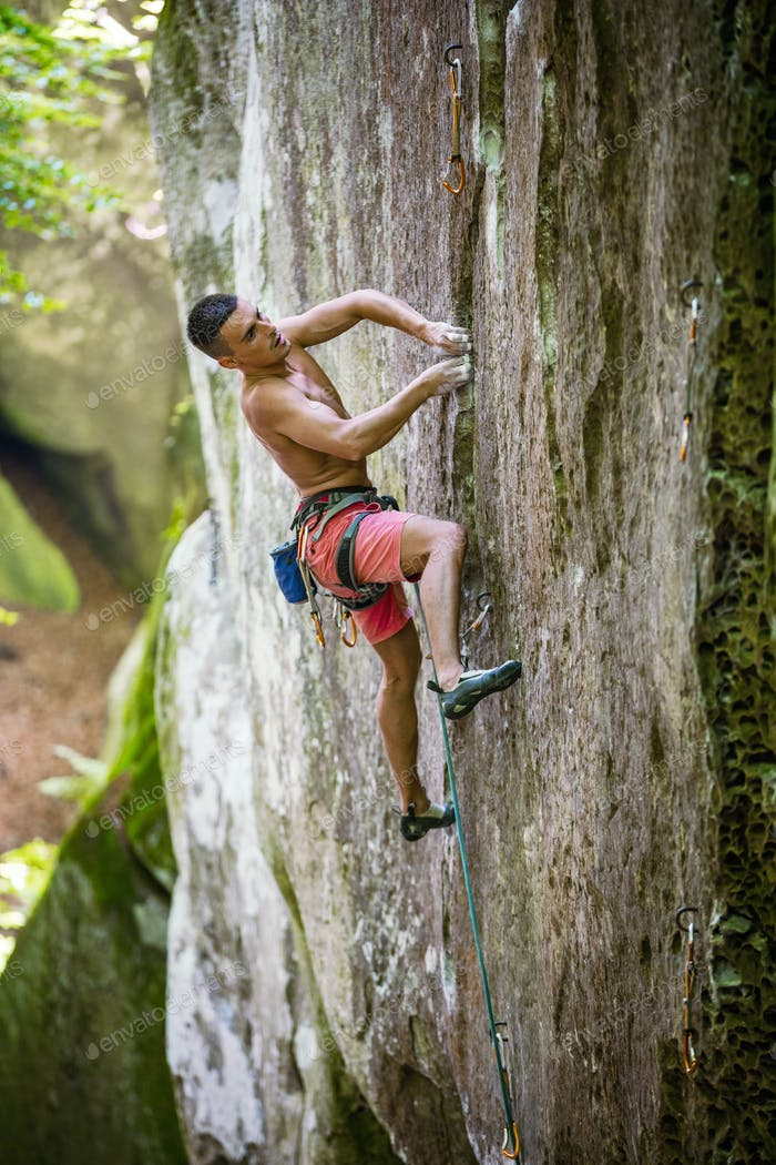 Rock climber on challenging route on vertical cliff