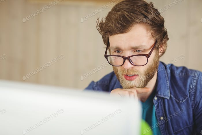Focused hipster working at his desk in his office