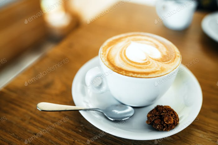Tasse mit heißem leckerem Kaffee auf Holztisch im Café, Nahaufnahme