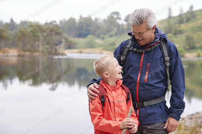 Grandfather and grandson standing on  the shore of a lake