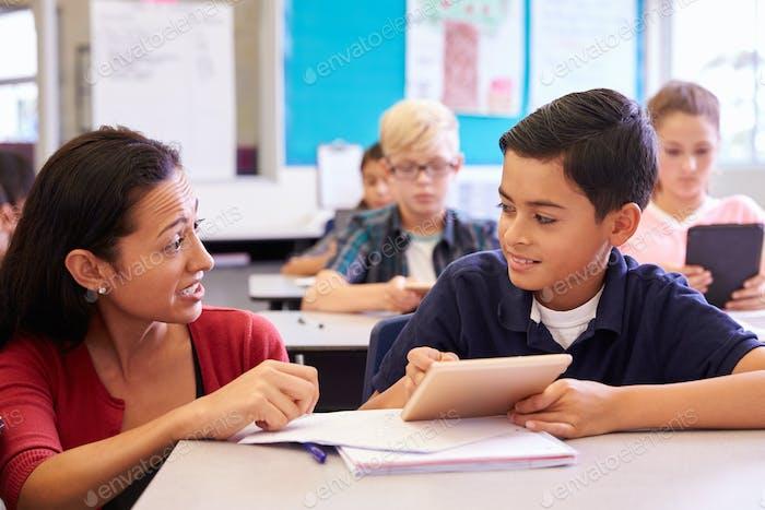 Teacher helping elementary school boy using tablet computer
