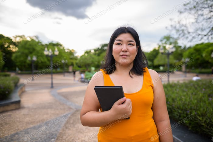 Beautiful overweight Asian woman holding book in park