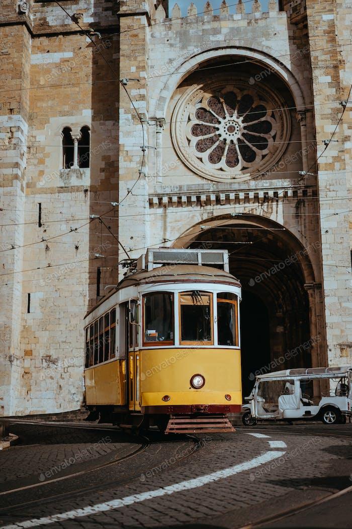 Die  malerische gelbe Straßenbahn fährt direkt vor der Kathedrale Se in Lissabon. Lissabon Lissabon Lissabon